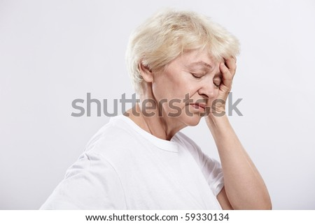 An elderly woman rests her head on a white background - stock photo