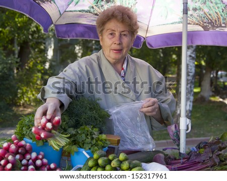 An elderly woman sells on the street herbs from the kitchen garden