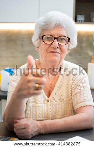 An elderly woman showing thumbs up sign.