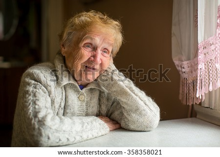 An elderly woman sits at a table near the window. - stock photo