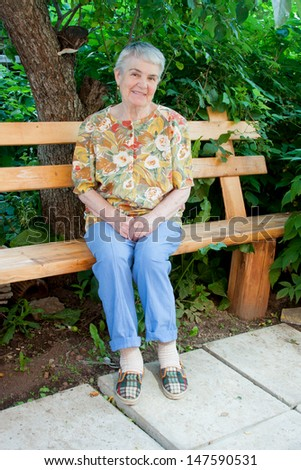an elderly woman sits on a bench in a garden