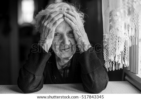An elderly woman sitting at a table in a depressed state.