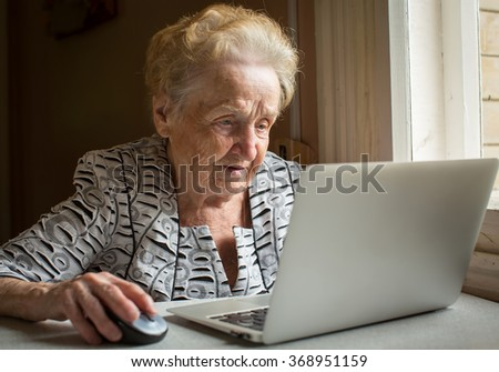 An elderly woman sitting at the table and types on laptop. - stock photo