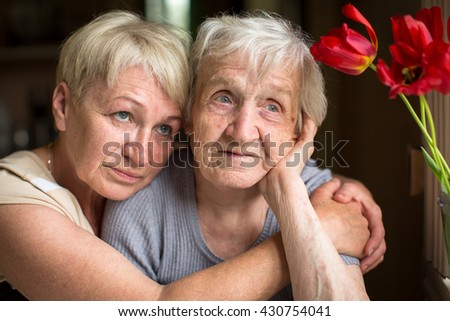 An elderly woman sitting in an embrace with his adult daughter. - stock photo