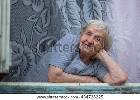 An elderly woman sitting on the windowsill. - stock photo