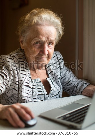 An elderly woman sitting with laptop. - stock photo