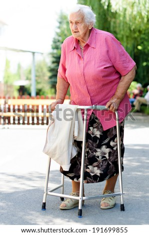 An elderly woman standing with her walker in nature - stock photo