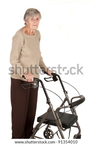An elderly woman standing with her walker isolated on white background - stock photo