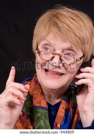 An elderly woman talks on the phone - stock photo