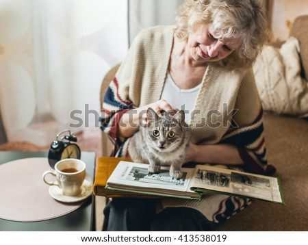 an elderly woman watching photo album with a cat on his lap - stock photo