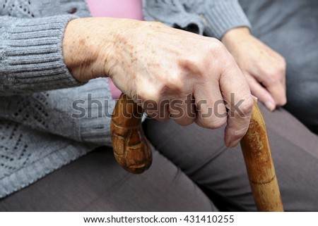 An elderly woman with a cane