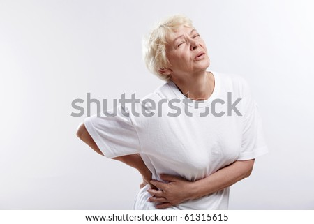 An elderly woman with a sick back on a white background - stock photo