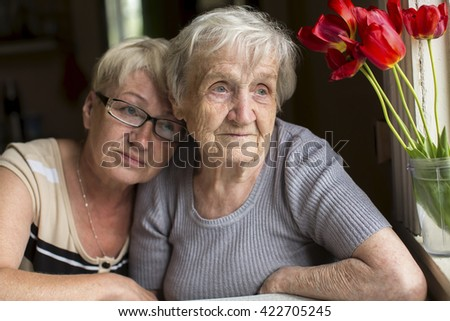 An elderly woman with her adult daughter. - stock photo
