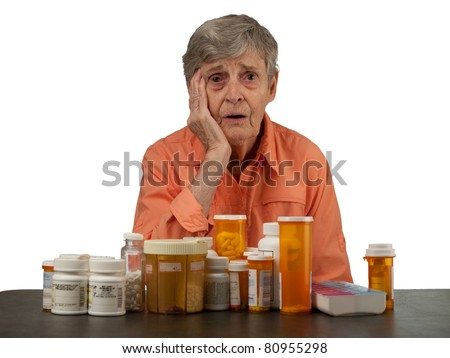 An elderly woman with medications looking overwhelmed - stock photo