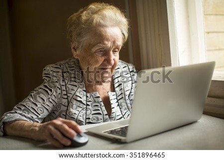 An elderly woman works on a computer. - stock photo
