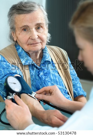An elderly women being examined by a doctor - stock photo