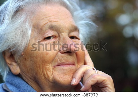 an elderly - 89 year old - woman looking into the camera and smiling. Shallow DOF. - stock photo