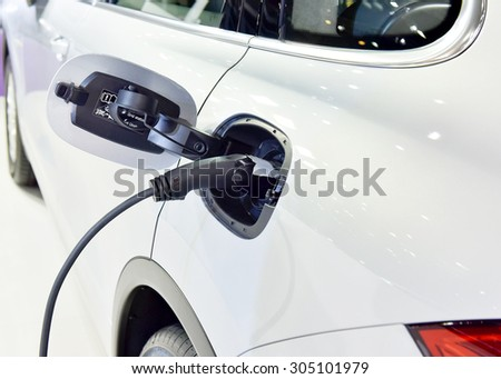 An electric car charging at a power station  - stock photo