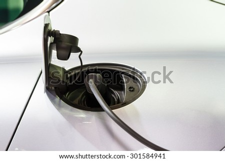 An electric car charging with the power cable supply plugged in,