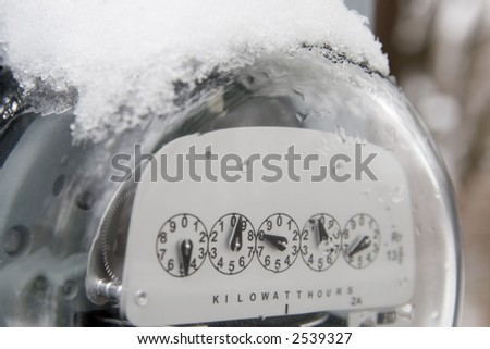 An electric utility meter with snow and ice on the top of it. Could be used to illustrate the soaring cost of utility bills during winter time. - stock photo