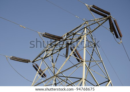 An electrical substation exhibits bolted, galvanized steel structures, cables, switches and insulators - stock photo