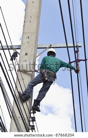 An electrical worker, on concrete pole, performs transmission lines repairing - stock photo