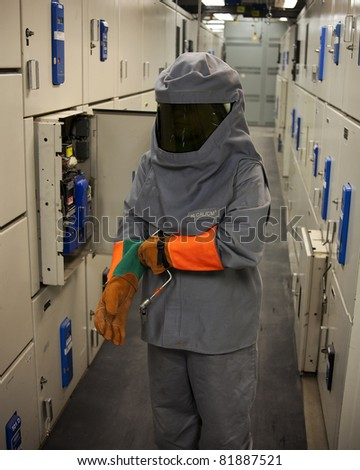 An Electrical worker wearing arc-flash protection.  The tool in his hand is used to draw out a large circuit breaker.