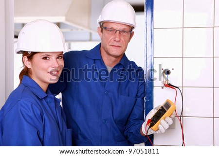 an electrician and his female colleague checking an electrical outlet