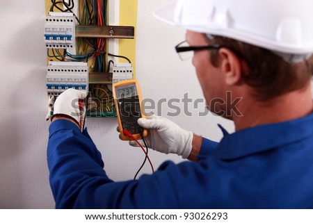 An electrician checking the energy meter. - stock photo