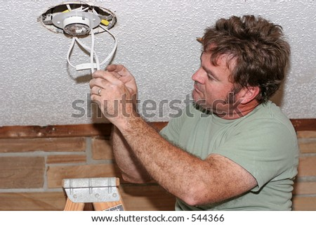 an electrician checking the switches on a light he's just installed - stock photo