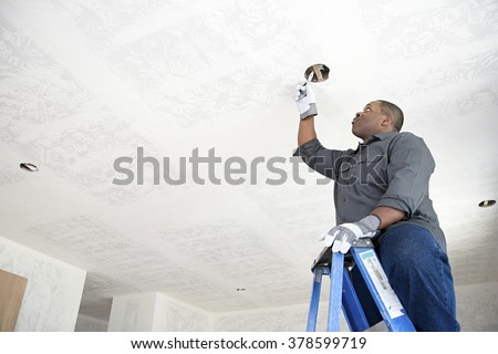 An electrician fixing wires - stock photo