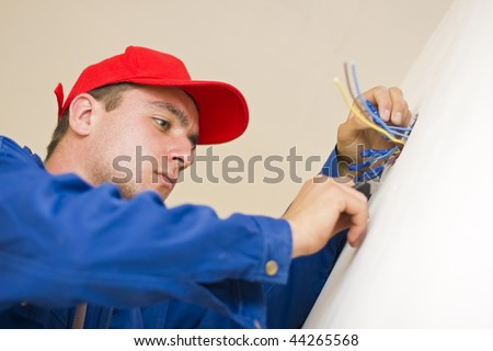 An electrician installing electricity in a new house. - stock photo