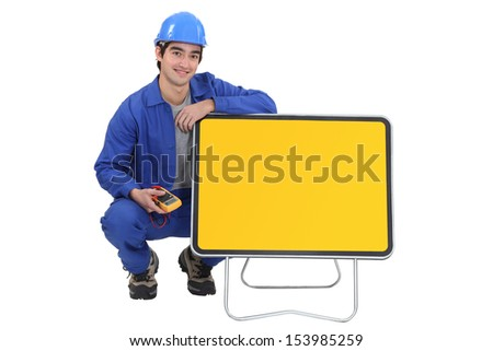 An electrician kneeled next to a blank road sign. - stock photo