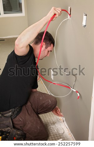 An Electrician working on a new construction site - stock photo