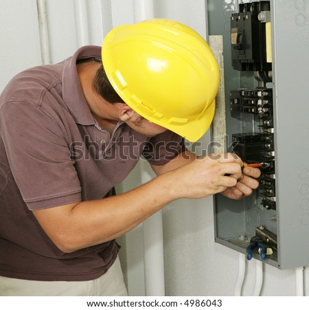 An electrician working on an electrical breaker panel.  Model is an actual electrician - all work is being performed according to industry codes and safety standards. - stock photo