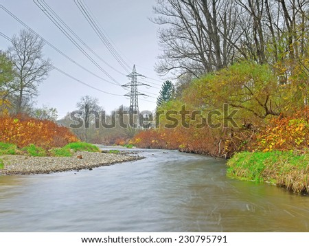 An electricity pylon on the shore of a river.  - stock photo