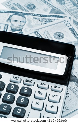 an electronic calculator on a pile of dollar bills, under business and finance concept - stock photo