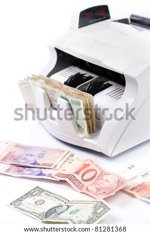 An electronic money counter processing bills - stock photo