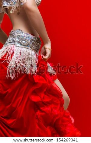 An Elegance red dress Belly dancer girl in action. With Red background - stock photo