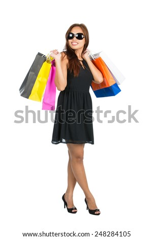 An elegant Asian female shopper in black dress, shoes, sunglasses flings many department store shopping bags over both shoulders while looking away from camera. Isolated. Thai national Chinese origin - stock photo