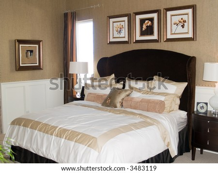 An elegant bedroom in tones of cream and white. - stock photo