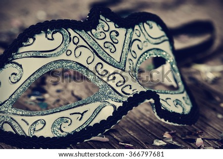 an elegant blue and black carnival mask on a rustic wooden surface, with a filter effect - stock photo