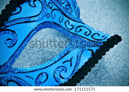 an elegant blue and black carnival mask on a sparkling blue background - stock photo