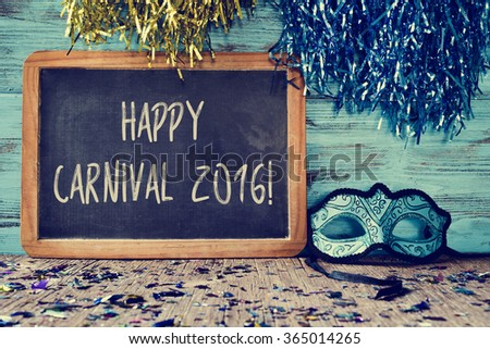 an elegant blue and black mask and a chalkboard with the text happy carnival 2016 on a rustic wooden surface full of confetti - stock photo