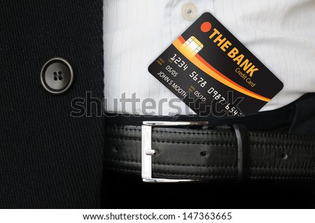 An elegant businessman holding a credit card under his trousers' belt, and showing it