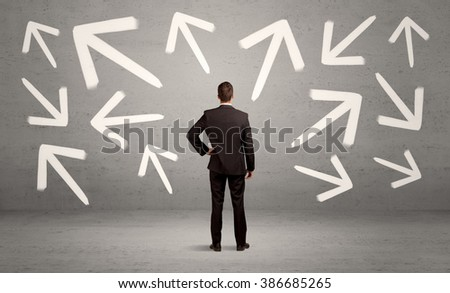 An elegant businessman standing with his back in front of urban wall full of arrows pointing in different directions concept - stock photo