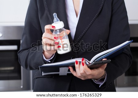 An elegant businesswoman working while holding her child's milk bottle - stock photo