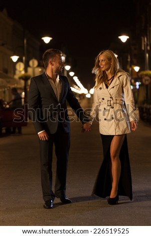 An elegant couple walking through a city at night - stock photo