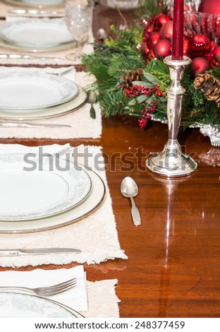 An elegant dining room table decorated for a Christmas dinner - stock photo