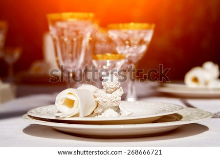 An elegant dining table setting with napkin and win glasses outdoors - stock photo